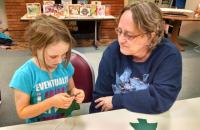 Grandparent and child sewing on buttons