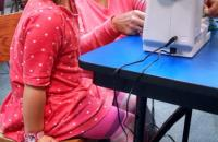 Child operating sewing machine with help